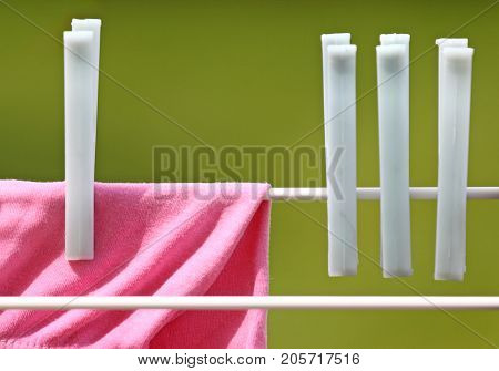 Clothespins hanging on clothesline against green background