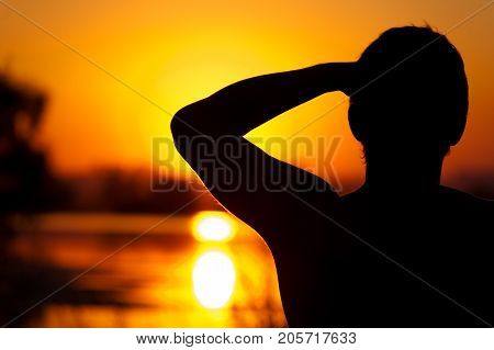 Silhouette of relaxed man enjoying sunset time, watching at river or lake water. Relaxation and leisure concept. Copyspace