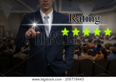 Businessman pointing five star button to increase rating of hotel over Abstract blurred photo of conference hall or seminar room with attendee background business evaluation concept Increase rating, 3D illustration