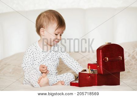 Baby Girl Playing With Her Mother's Jewelry Sitting On A Bed In Pajamas