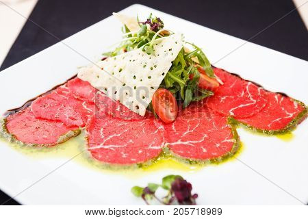 Beef carpaccio with salad and Parmesan cheese