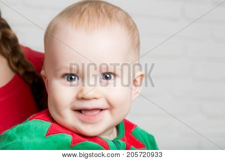 Elf kid in costume of santa. New year baby on hand of mother. Winter holiday and vacation. Xmas party celebration. Christmas child with happy face.