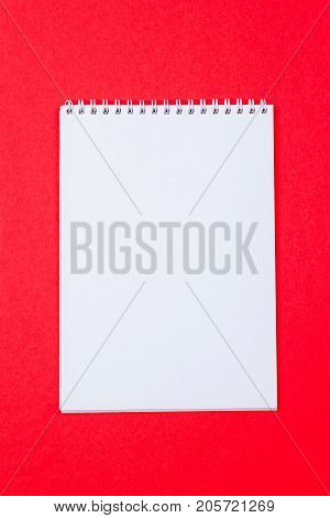 Top view of open spiral blank notebook on red paper background