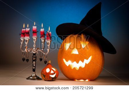 Halloween pumpkin with a candlestick, funny face face on a blue background