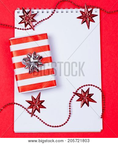 Holiday decorations and notebook and gift on red background