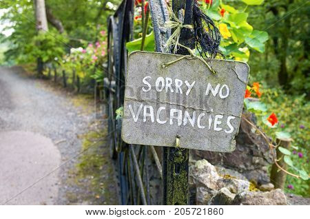 """""""Sorry No Vacancies"""" sign in garden of a bed and breakfast. poster"""