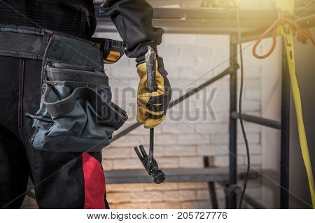 Construction Site Contractor with Hammer in Front of Scaffolding. Closeup Photo.
