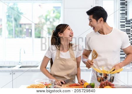 Young asian woman cutting slice vegetables making salad heathy food with fruits and man cooking menu for dinner in kitchen at home couple together romantic