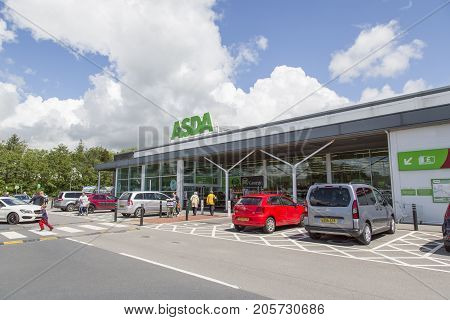 Swansea, UK: May 22, 2016: Shoppers enter and leave a busy Asda store. Cars are parked in the disabled spaces nearest to the entrance. Asda Stores Limited is owned by American Wal-mart.