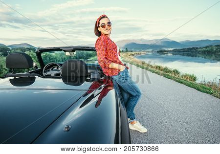 Young woman stand near cabriolet car on the road with beautiful mountain lake view.