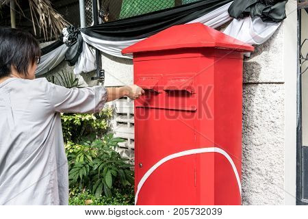 Asian woman posting a letter to red postbox or mailbox on street