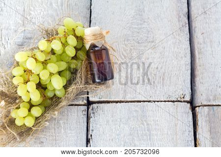 Healing grapes seeds oil in a glass jar fresh grapes on old wooden background seed extract has antioxidant and nourishing the skin spa concept. Bio eco products.