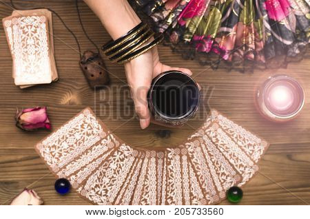 Fortune teller female hands and tarot cards on wooden table. Divination concept.