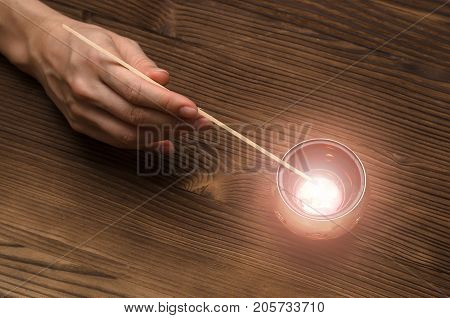 Fortune teller lights the candle on wooden table. Divination concept.
