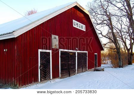 Old red ocher wooden outbuilding with wide and normal doors.