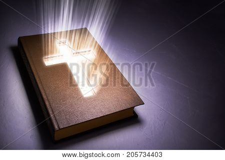 The book of the Bible from the inside glows a cross. Copy space for text. 3D rendering