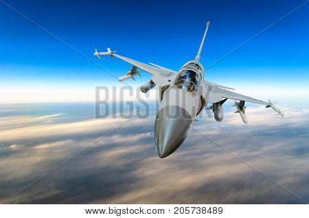 Military Fighter Jet Against A Blue Sky With A Backlight From Below.