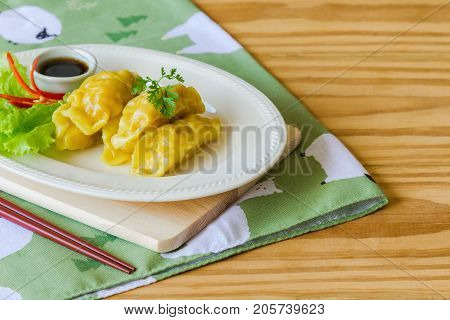 Homemade minced pork dumpling on white plate served with dipping soy sauce on wood table with copy space. Delicious dumpling or dim sum for breakfast or dinner. Dim sum or dumpling is Chinese food. Dumpling or dim sum ready to served.