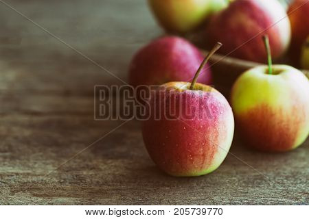 Stack of fuji apple and in basket put on wood table for background or wallpaper in vintage tone style. Delicious sweet and juicy fuji apple for salad cooking or bakery.Fuji apple has origins in Japan. Prepare apples for cooking or bakery.
