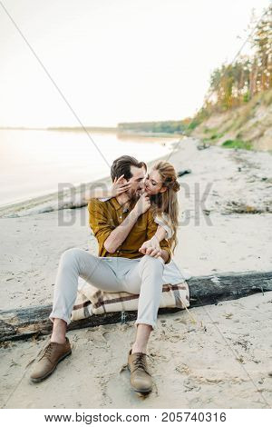 A young couple is hugging on the beach. Beautiful girl embrace her boyfriend from back. Wedding walk. A newlyweds looks at each other. Artwork, soft focus