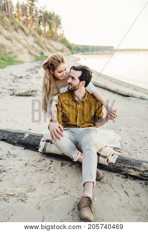 A young couple is having fun and hugging on the beach. Beautiful girl embrace her boyfriend from back. Wedding walk. A newlyweds looks at each other. Artwork, soft focus