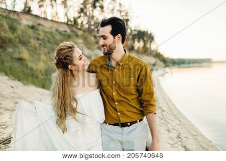 A young couple is having fun and walking on the sea coastline. Newlyweds looking at each other with tenderness. Romantic date on the beach. Wedding. Artwork, close-up image