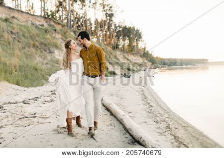 A young couple is having fun and walking on the sea coastline. Newlyweds looking at each other with tenderness. Romantic date on the beach. Wedding.