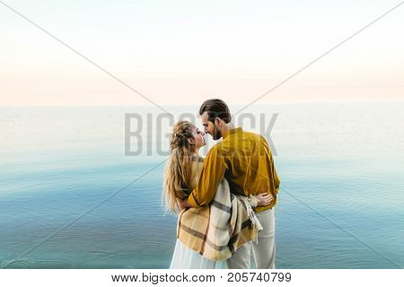 A beautiful couple is embracing on the sea background. Moment before the kiss. Romantic date on the beach. View from the back. Wedding. Artwork, soft focus