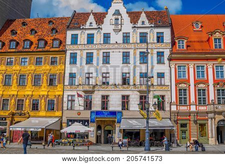 Wroclaw/Poland- August 17, 2017: cityscape of old town Market Square with colorful ornate historical buildings, shops and restaurants, citizens and tourists walking around and sitting on benches