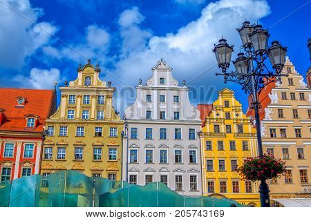 Wroclaw/Poland- August 17, 2017: cityscape of old town Market Square with colorful ornate historical buildings, street light, decorated with flowers, over blue sky with clouds