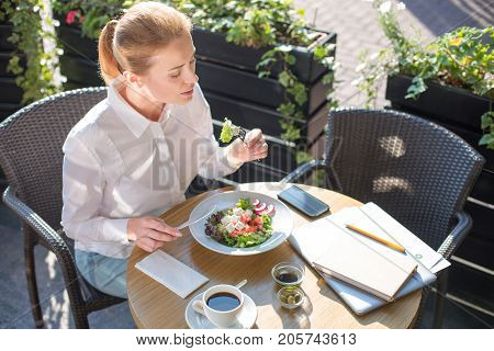 Lunch time. Charming young woman sitting at the table on the terrace of a restaurant and eating a delicious salad during a break at work