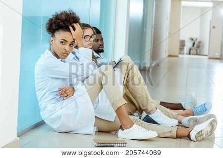 Three young medical interns in white robes sitting on a floor in hospital