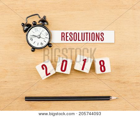 Resolutions 2018 new year red on wood cube with pencil and clock top view on wood tableNew year business concept