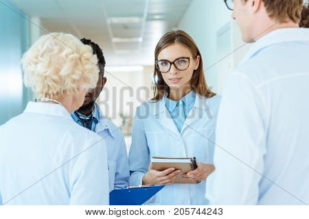 Young doctor in lab coat and glasses holding notebook and discussing work with colleagues