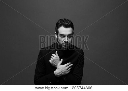 Black and white portrait of a young handsome man in all black suit, hands crossed on the chest, looking at the camera, against plain studio background.