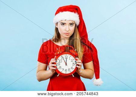 Xmas seasonal clothing christmas time concept. Sad woman wearing Santa Claus helper costume holding big red clock waiting for celebration