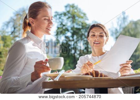 Best mentor. Upbeat pretty woman holding a printout and explaining the data on it to her new colleague while having a lunch with her in a cafe