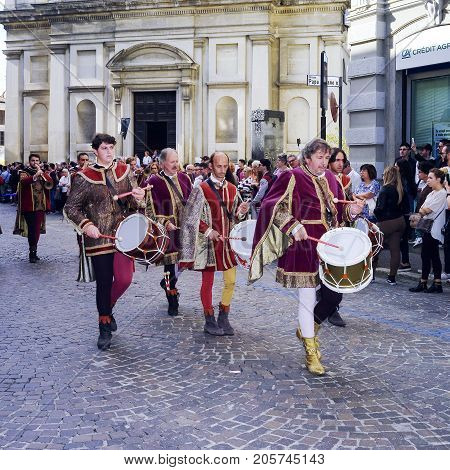 MORTARA, ITALY - SEPTEMBER 24, 2017: some drum players, dressed in Reinassance costumes, parade through the streets of Mortara (Lombardy, Pavia Province, Northern Italy) during a medieval reenactment known as Palio dell'Oca; some viewers are looking at th