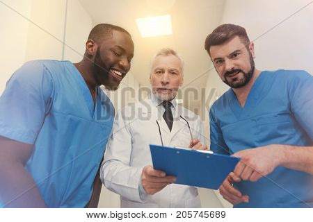 Have a look. Attentive professor standing between his interns and holding folder while being very serious
