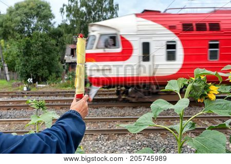 The train is passing by the railway worker with a flag. Latvia