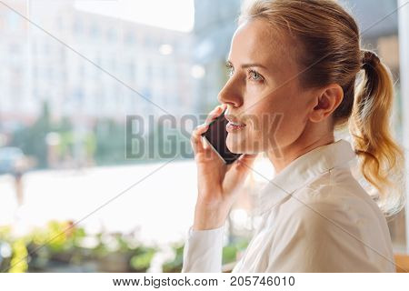 Crucial call. The close up of a beautiful young woman sitting in the cafe near the window and talking on the phone