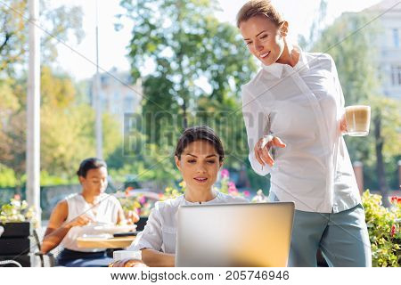 Important advice. Charming young woman standing near her colleague working on a project on a laptop and giving her a piece of advice while holding a cup of latte