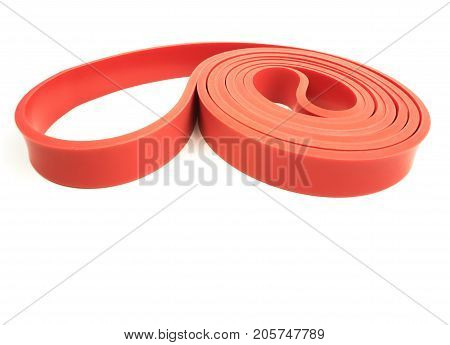Red exercise resistance band on a white background with writing space