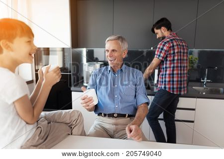The man washes the dishes, and behind him his elderly father and his little son are laughing at something, sipping tea from mugs.