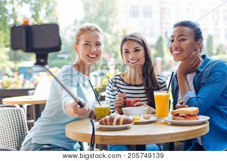 Best friends. Three gorgeous young women sitting in a cafe and taking a selfie together, using a selfie stick