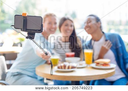 Best friends forever. The focus being on the selfie stick of three beautiful young women sitting on the terrace of a restaurant and taking selfies