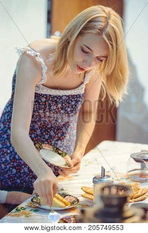 young woman serves food serves table with cake.
