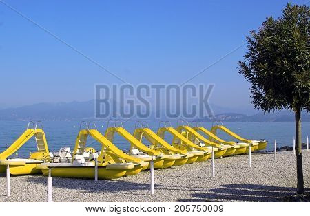 row of yellow pedal boats with slide at the beach of Peschiera Lake Garda Italy