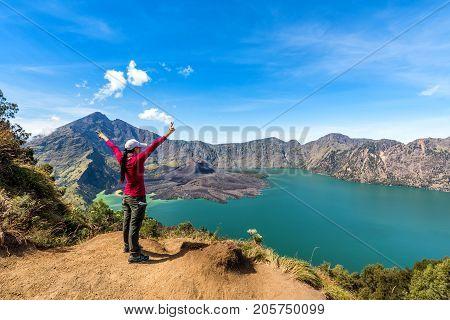 Woman spreading hand enjoy and happy with active volcano Baru Jari Lake Segara Anak and summit of Rinjani mountain view after finished climbing at Rinjani mountain Lombok Indonesia.