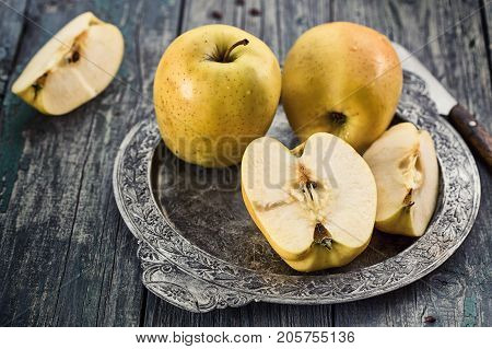 Yellow apples on a metal tray in rustic style